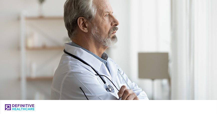 An older white male doctor looking out a window with a thoughtful expression