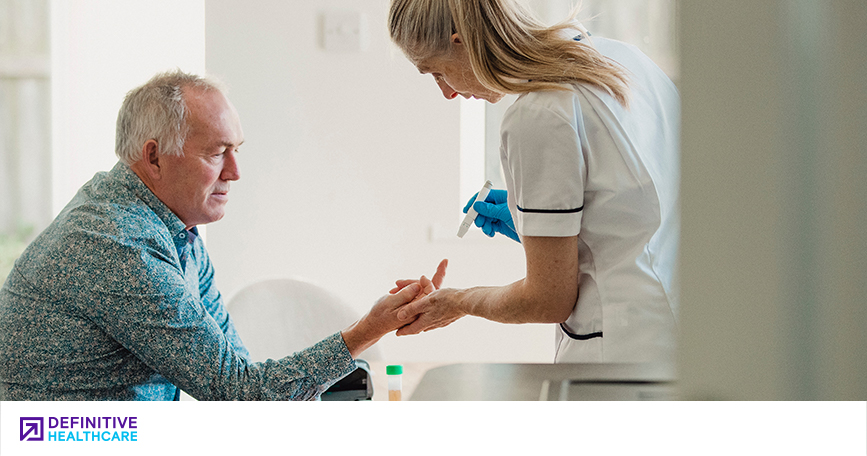 An older man getting his blood drawn from his finger by a healthcare professional